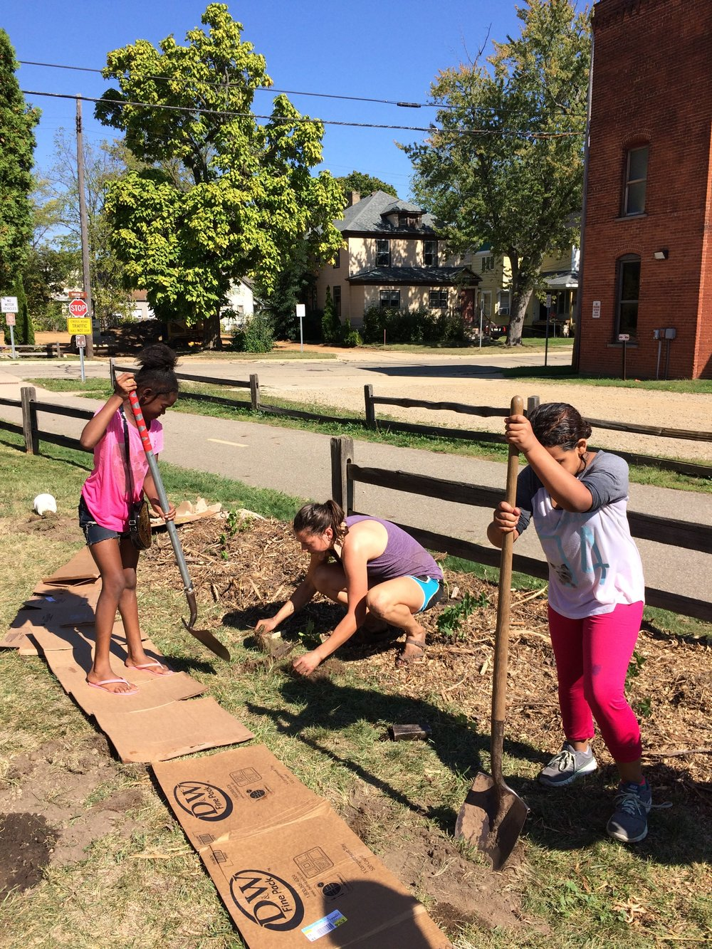 Kalamazoo youth digging in and planting trees along the Kalamazoo River Valley Trail