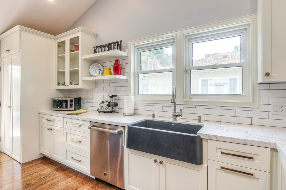 The bright and colorful kitchen features custom built shaker cabinets, Caesarstone quartz countertops, Bosch appliances and farmhouse style Blanco sink.