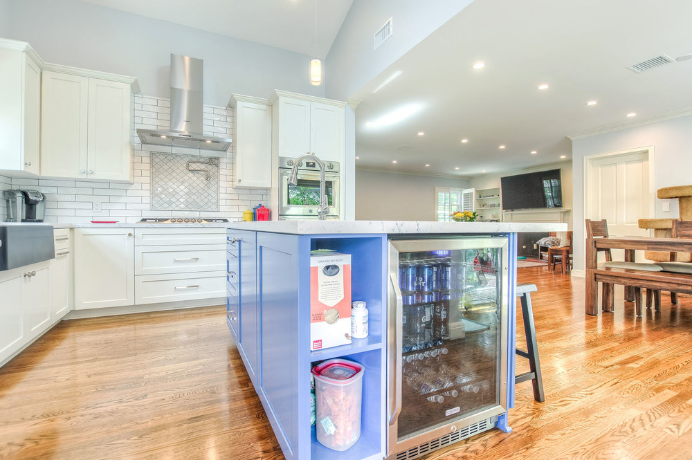 To add a focal point and a pop of color to the all-white bright kitchen we created a custom island in blue with an extra sink, storage space and a wine cooler.
