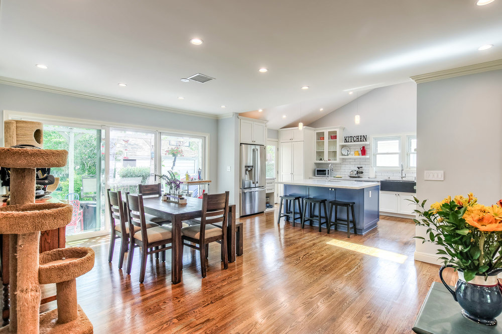 The small and boxed kitchen and dining room were combined with an open floor plan and include raised vaulted ceilings and skylights in the kitchen area to create a roomy and airy space.