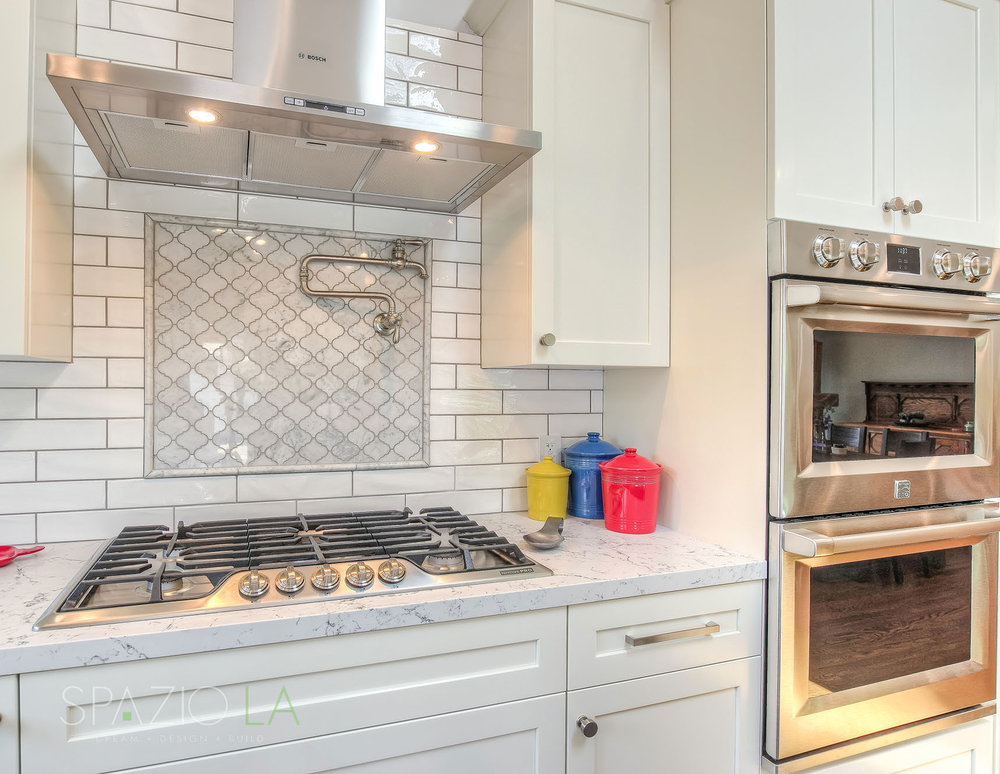 Cooking area with Bosch cooktop and separate ovens, pot filler, white subway tiles for backsplash and grey accent arabesque tiles.