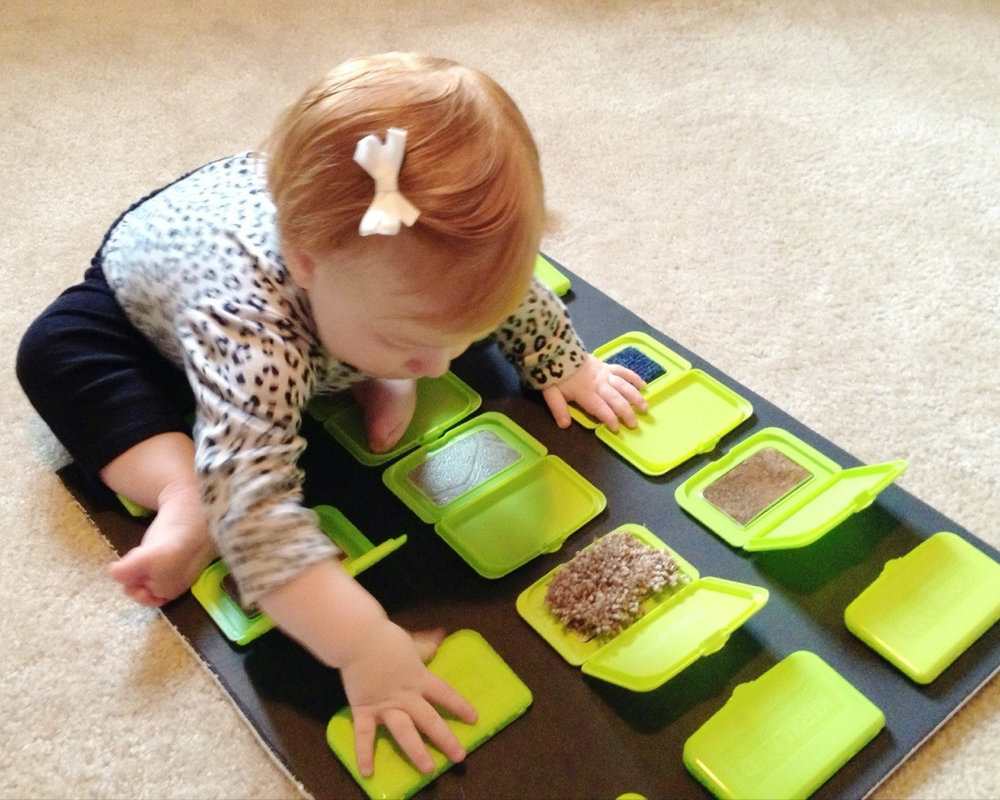 Save up and reuse baby wipes lids to make a peek a boo sensory board. Find out how this one was made from  Motherhood and other adventures .