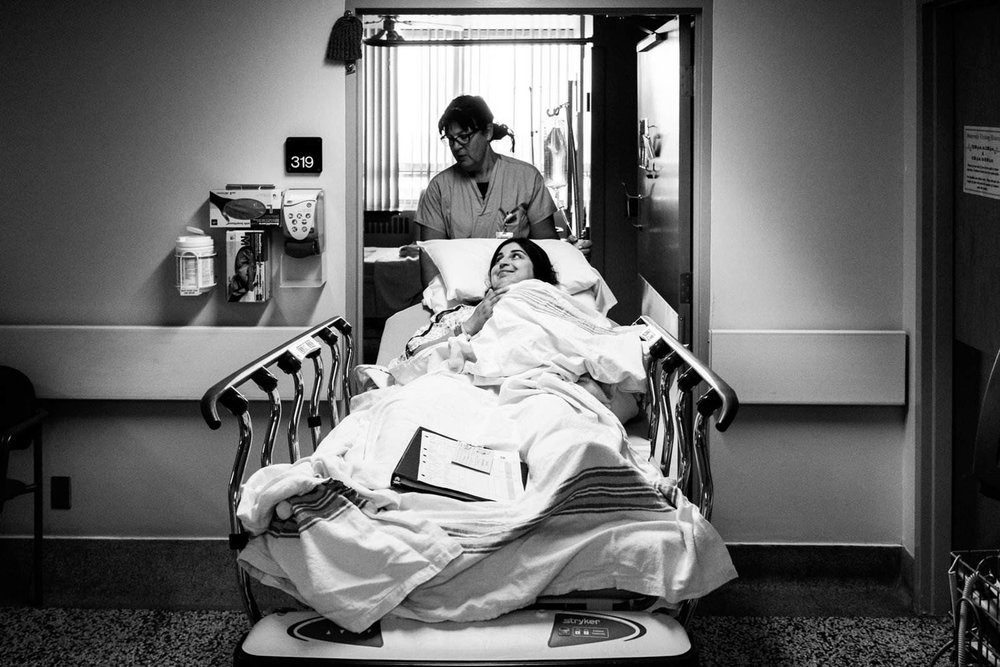 expectant mother being wheeled into a birthing room