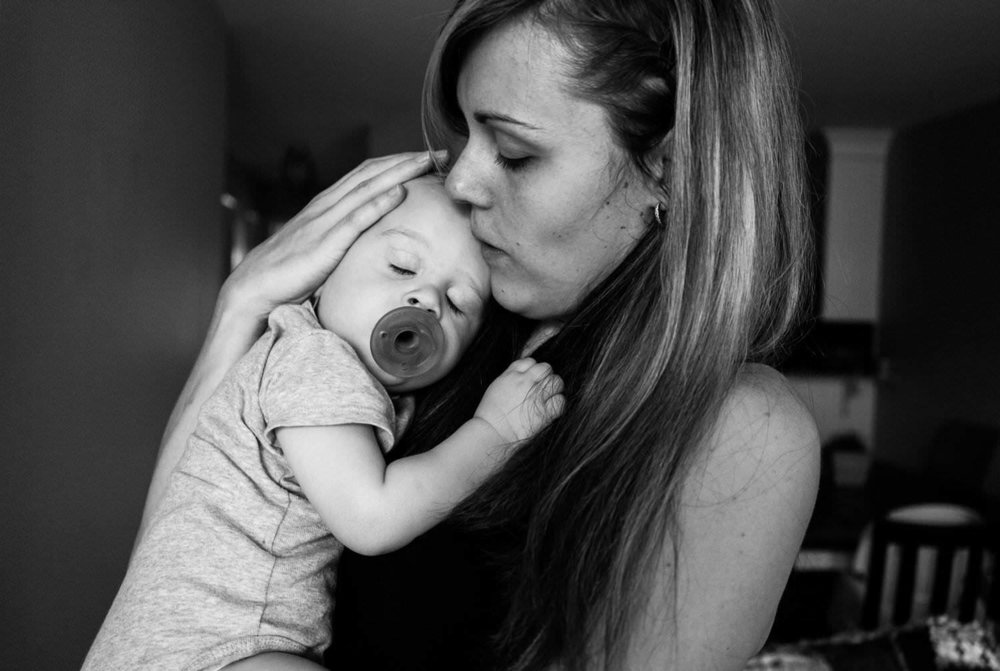 mother tenderly holding a child with a pacifier