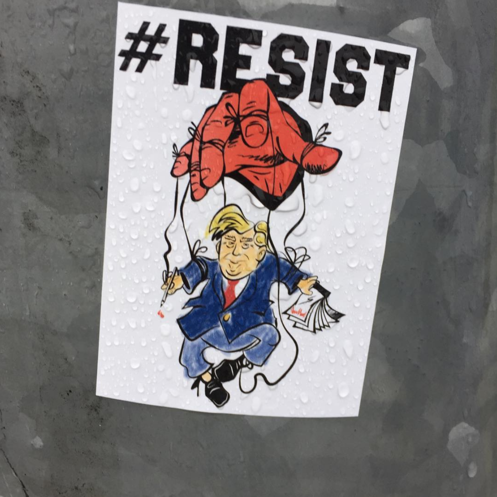 "Copy of Picture of President Trump as a marionette doll controlled by a red hand with the caption ""#RESIST"""
