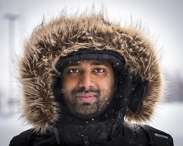 Joseph Philiph, a Niagara College Student, poses for a photo during an oncoming snowstorm. Crews worked overtime around the campus to clear the snow.