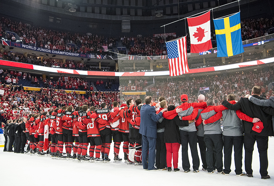 Team Canada watches as their flag is raised following their victory at the 2018 IIHF World Junior Championship.