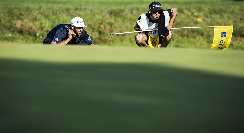 Dustin Johnson reads the green prior to making a putt at the RBC Canadian Open.