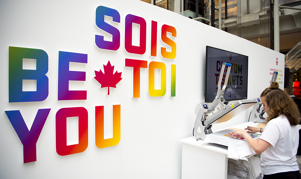 """A staff member creates a custom t-shirt at Team Canada's """"Be You"""" pop-up shop during Pride Toronto."""