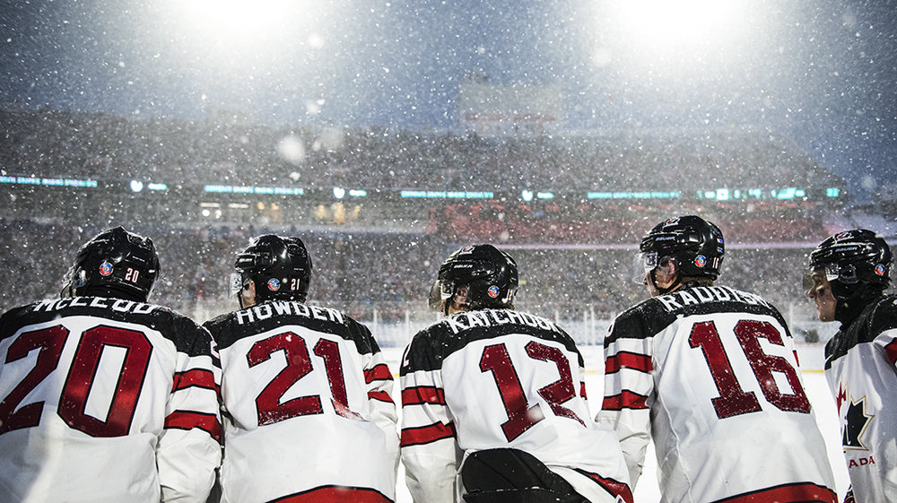 Team Canada's (L-R) Michael McLeod, Brett Howden, Boris Katchouk, Taylor Raddysh and Robert Thomas watch from the bench during the 2018 World Junior Championship's outdoor game against the United States.