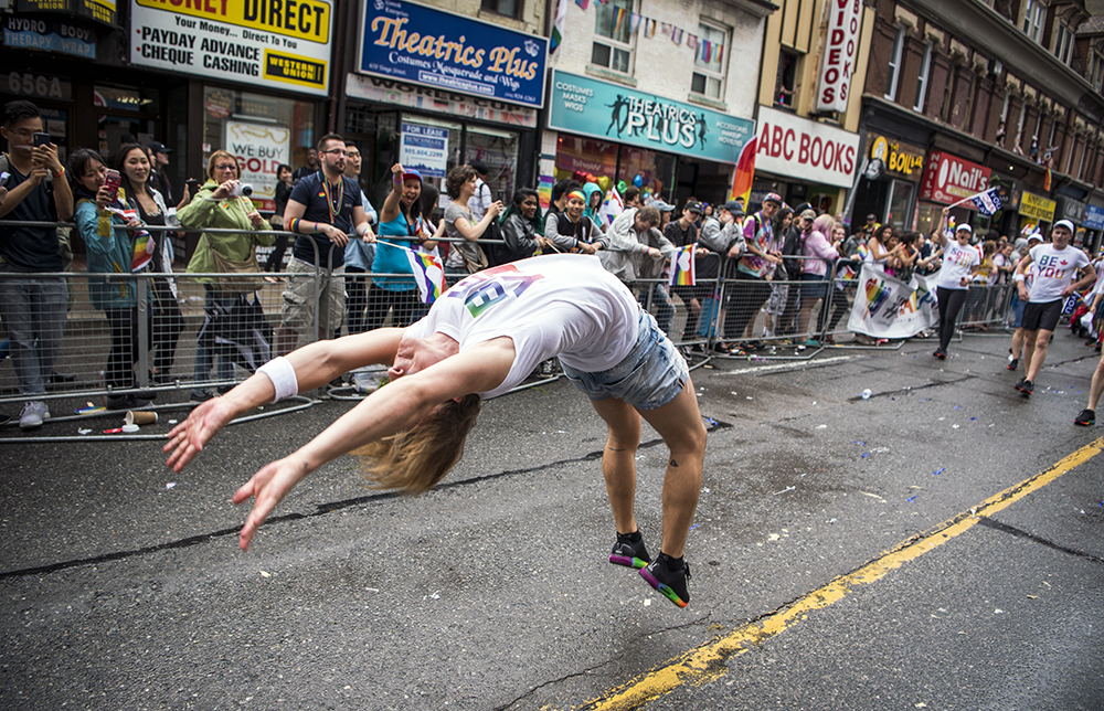 Vincent Lavoie does a flip during the Toronto Pride Parade, while marching with the Canadian Olympic Committee.