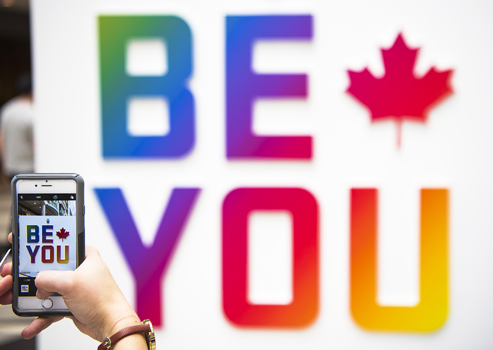 """A staff member takes a photo of the """"Be You"""" sign at Team Canada's pop up store."""