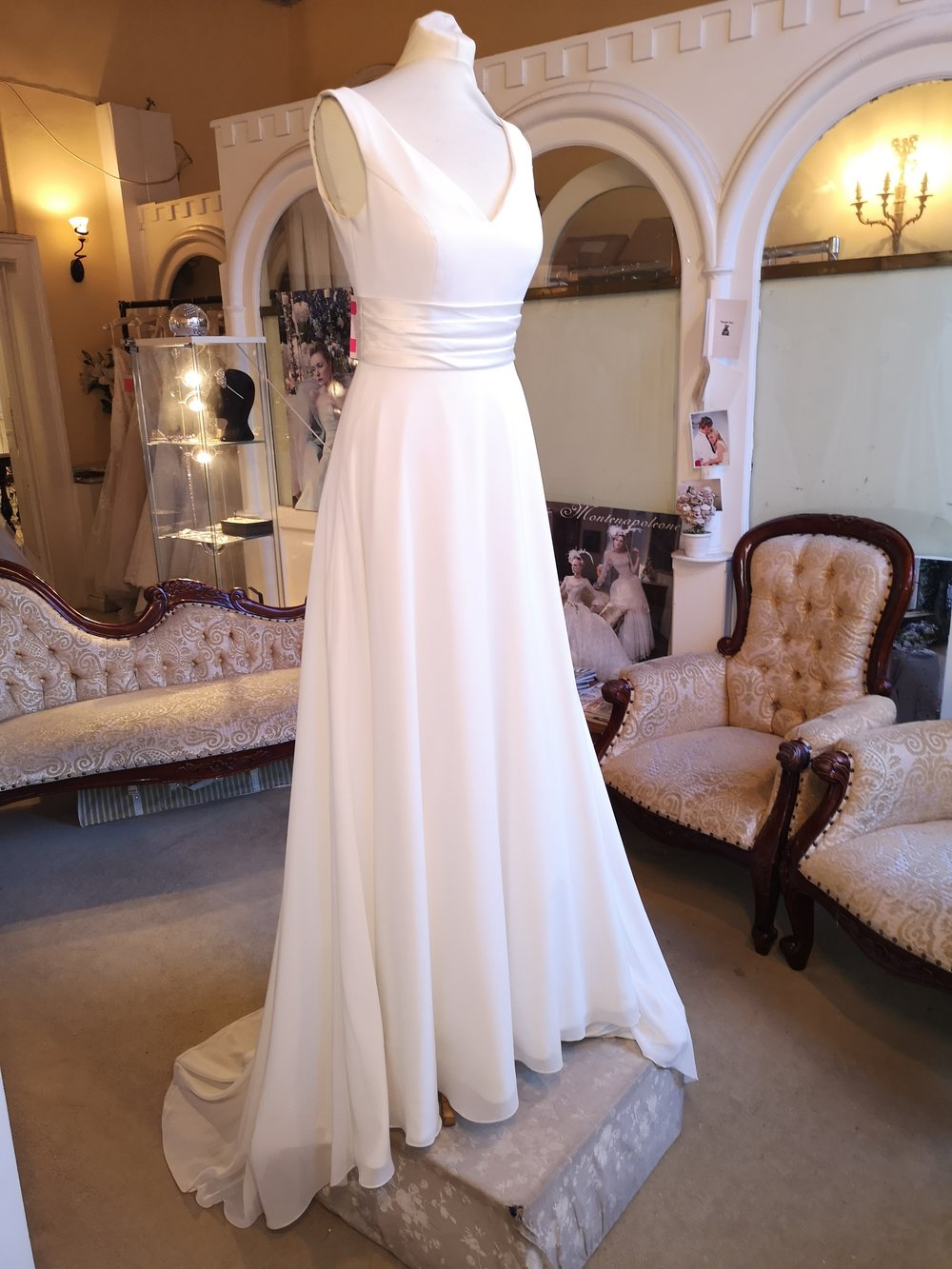 WHITE ROSE CHIFFON A LINE DRESS WITH SATIN BELT DETAIL. V BACK WITH BUTTONS  WAS €1,395 NOW €799  COLOUR : IVORY  SIZE : 10