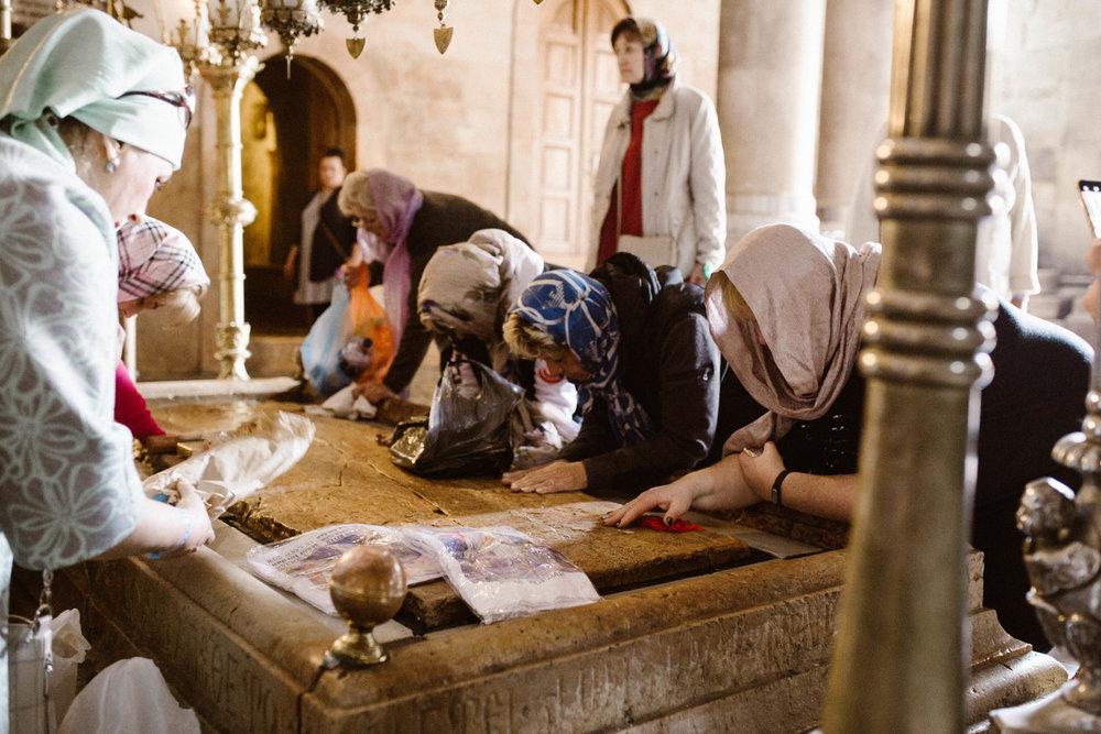 Women praying on the stone where Jesus's body was prepared for burial