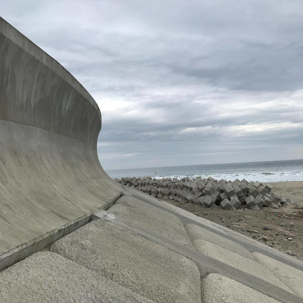 October 10, 2017  #Fukushima  and  #Miyagi  update: One of the most profound environmental landscape changes I've ever seen is the wall that's been built between the sea and land in northern  #Japan . The wall rises about 10 meters (30 feet) and extends for hundreds of kilometers or roughly the equivalent of the distance between Washington DC and Providence Rhode Island which is the swath of land that the tsunami struck. Sadly the wall shuts off the sea from view and produces a walled in existence severing the connection to the sea that's existed in  #Japanese  culture since the beginning of its existence. The inspiration of those magnificent wood block prints and poems now obscured behind a cold flat wall. What the wall is also blocking is centuries of knowledge that's been passed down: farmers used to be able to read the tides because they'd flow forth from the ocean into land letting them know about tsunamis and other events-blocked off we are apart from it and I'd also apart forms an essential part of our collective human existence. I wonder if children born here now will even know what lies behind the wall if their parents don't take them up the high steps that Overlook the watery horizon? On the part of the authorities, walling it off is an act of massive denial: sea levels are still rising and the sea is still there, it's not going away. By building this concrete monolith we are turning our back on the wonder and love of something that has sustained us since the beginning and replacing it with a false sense of security. Ultimately we have only one choice with the sea: understand it and move with it or await it to breach our shortsighted strategies that only benefit the producers of concrete.