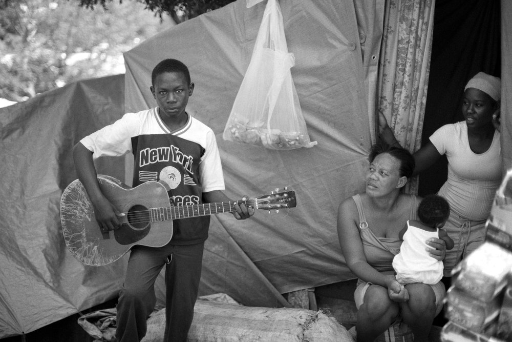 January 22, 2018   Haiti remembrance, day 6  I was always taken by this young man's intensity. He reminded me of Bob Dylan's hungry insight when he was younger. Taken in the Petonville camp this guitarist sung of the hard conditions there and was well respected by all those who found themselves living there in the earthquake's aftermath.  I know I've taken a couple days off presenting here, but it hasn't been for lack of interest—I've been at an intense and informing fellowship at the Dart Center at Columbia University looking at how trauma affects us, leaving me with no time to write outside of the fellowship. However the time spent there has helped me better understand the trauma caused by the earthquake in Haiti.  I also think it's fitting to be posting now on the third day of the US government shutdown. Looking through my photos of Haiti, I can't help but think that so many here in the US take the government and all that it provides for granted and should be more thankful for the things that it does and does very well from running our national parks to making sure that the elderly have the benefits they deserve after contributing a lifetime to this country. It's inconceivable to me that the most powerful and wealthiest nation on earth can just shut down the government. Isn't a closed government because of an incompetent and corrupt leader one of the hallmarks of a shithole country and one one that can only lead to decline unless that county starts valuing the great instutions it spent so much effor building?  As the United States defunds its institutions, does not invest in education and health, I fear that our future will look more like Haiti's where the wealthy live high above the city while the great majority of the population waste their time time fulfilling basic needs while lacking a good education for advancement.