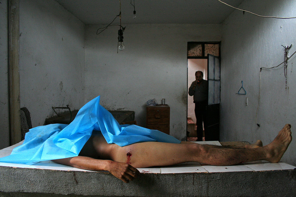 A corpse lies on an examining table in a police station. The victim's house was sprayed with bullets after which assialants entered the house and executed him.