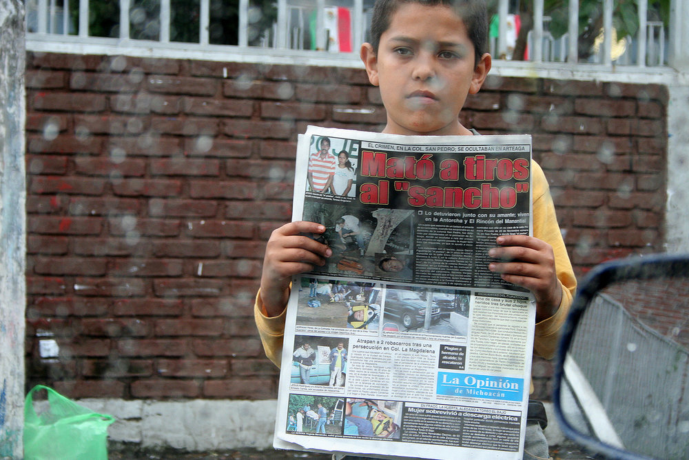 A young boy sells news papers at an intersection in Uruapan, Michoacán State. Taken in 2006, I wonder if this boy is still alive, or joined a cartel or fled to The United States.