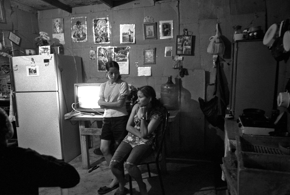 "Teresa Gómez, who started working in a Tijuana maquiladora at age 15 (she is now 16) sitting.  She lives in Nueva Esperanza with her mother Sara, not pictured.  Sara makes batteries at the Sanyo Electric Co. maquiladora, one of Tijuana's largest: ""My shift is from 7-5; then come other workers for the night shift from 5-1:45. I'm from Veracruz. There was no work there and no schools for my kids. I've been here [Nueva Esperanza] for about five years. We built this house ourselves. We're on this little slope because when it rains the water comes through the village. It's an awful river full of plastic and trash. This place can get dirty. Trucks come, I'm not sure from where, and dump their trash in the river. We try to organize clean-ups. My daughter Teresa started at the maquilas at 15. We asked the company if she could start early. I signed a form to allow that.""  Teresa: ""I work for Marcos Calidad. They manufacture wooden frames and mirrors. I mostly cut glass. I've been there a year and make Ps750 a week ($75). No raise yet. Most of my friends work at the factories here. It's okay. I'm don't plan to leave."""