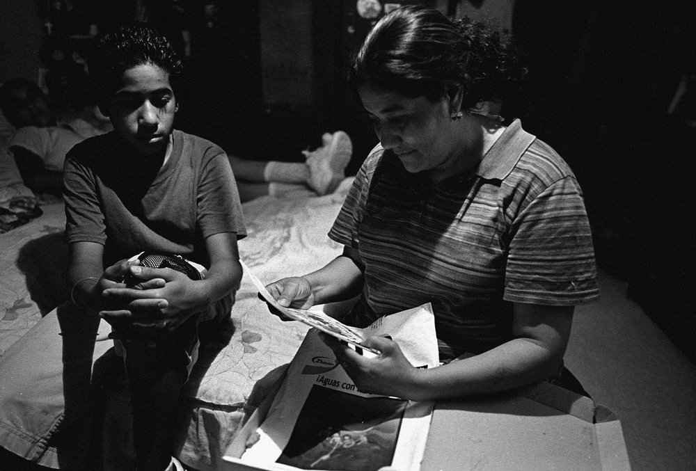 "Lidia Orozco, 35, mother of 2 in the Colonia Robledo, in Mexicali that sits next to several industrial parks. She is looking over learning materials for a class she plans to take at a nearby college.  ""This place is a mess, a dump. The streets are unpaved and the dust is filled with chemicals. We may be poor, but we don't want this factory trash here. It affects me. I cough and have asthma. I think that the municipal government is responsible for looking after what the factories throw out in the air. I'm not sure. I'd like to see a vocational school open up here instead of a factory. There's nothing like that here. Before NAFTA there were fewer cars. You could count them pass by on the street. Now there are so many. Sometimes we just laugh at how much it's changed. I don't understand NAFTA very well."""
