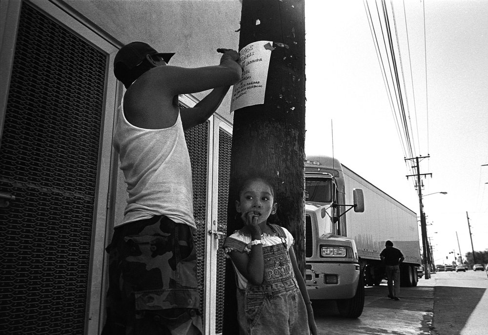 "Jorge Arredondo, 31, hammers a sign to advertise his juice business; next to him is his daughter Guadalupe, 4.  Jorge worked in a factory in Tijuana before the factory closed. He now sells juice street side in an industrial park.  ""I moved here from Guanajuato. I worked at the factories but lost my job when a factory closed up over the weekend. I came to work and my co-workers were outside waiting to see if the bosses would show up again. They didn't. They still owe us our final pay."""