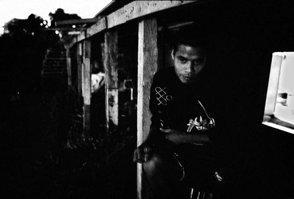 """Jesus Ruiz pictured on his porch in the Nueva Esperanza slum. He and his family, migrated from Mexcaltitan, a tiny island off Mexico's Pacific coast. At 16, Ruiz settled with his family at the edge of the low-income community of Colonia Chilpancingo in Tijuana, about a mile from the border. After assembling a home from wood and cardboard scraps, the Ruiz family found work at the factories. Soon the area was solid with shacks as Mexico's poor and jobless arrived seeking work. He has managed steady factory work and says that his current job, making bandages and IV bags at the US-owned Tyco International plant for $70 a week, is a good one. """"At least it's clean. I made auto parts before and my hair and face were caked with dirt."""""""