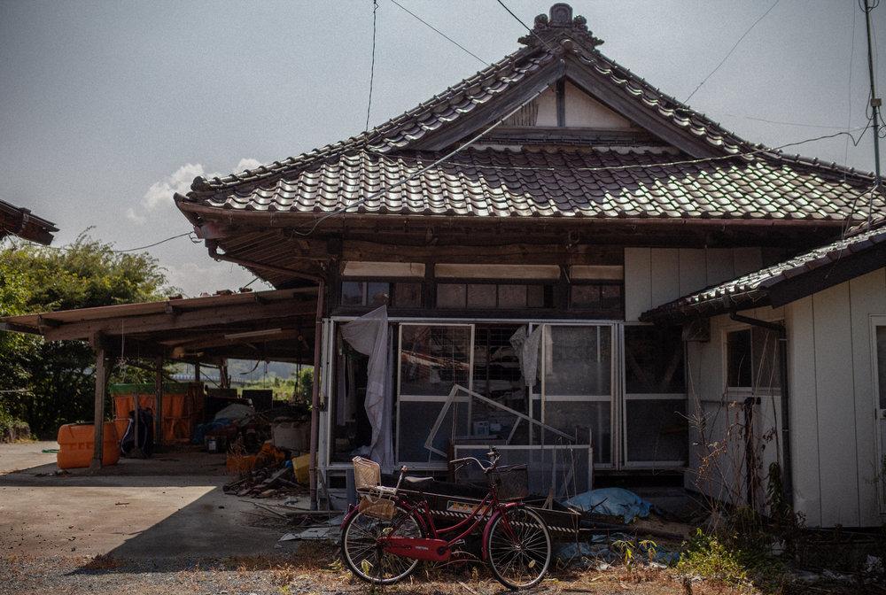"""「ただいま」と 主なき家に 声かける 懐かしき匂いに 声あげて泣く""""I'm home,"""" I cryas I enterthe empty house –my voice respondingto the familiar smells - 半杭 螢子 (福島県 2011年5月)Keiko Hangui, Fukushima May 2011"""