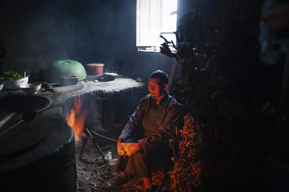 A peasant cooks in a traditional oven in Hunan Province, China.