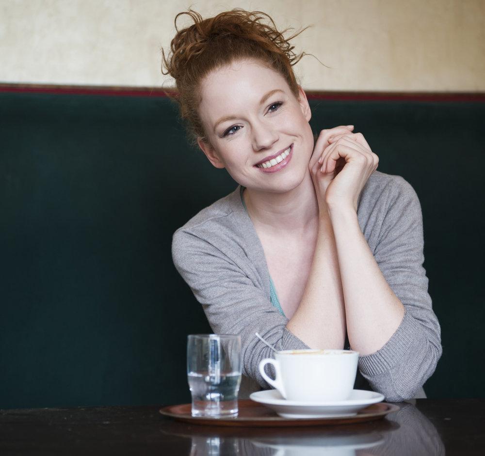 Weibliches Model Antonia lachend im Café