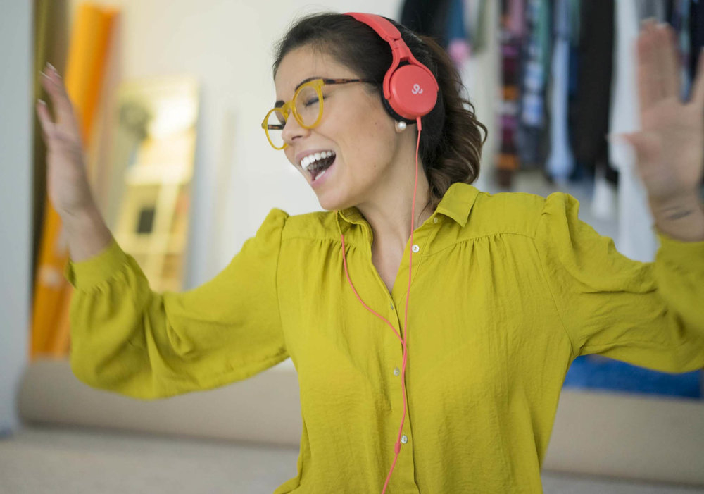 Thanee hört Musik in gelber Bluse