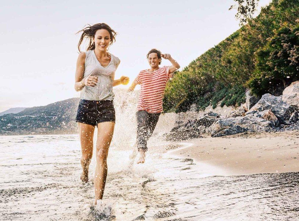 Model Nicola rennt glücklich am Strand in der Sonne