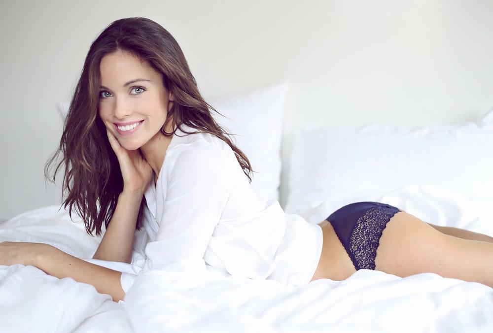 Model in weißer Bluse liegt verspielt im Bett