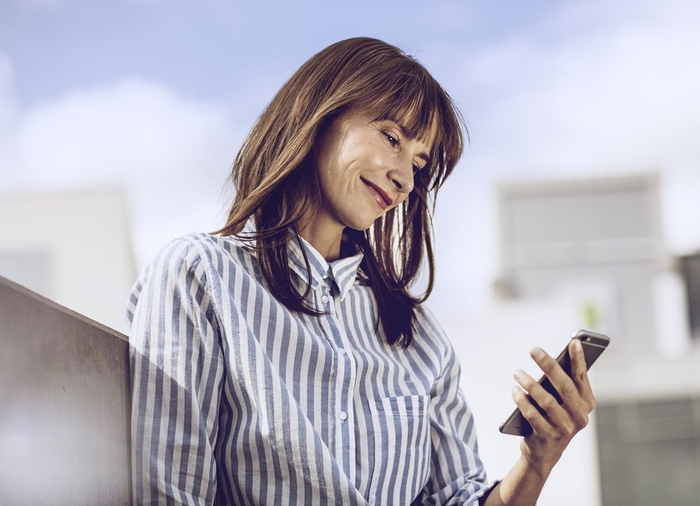 Anne im gestreiften Hemd schaut auf ihr Handy