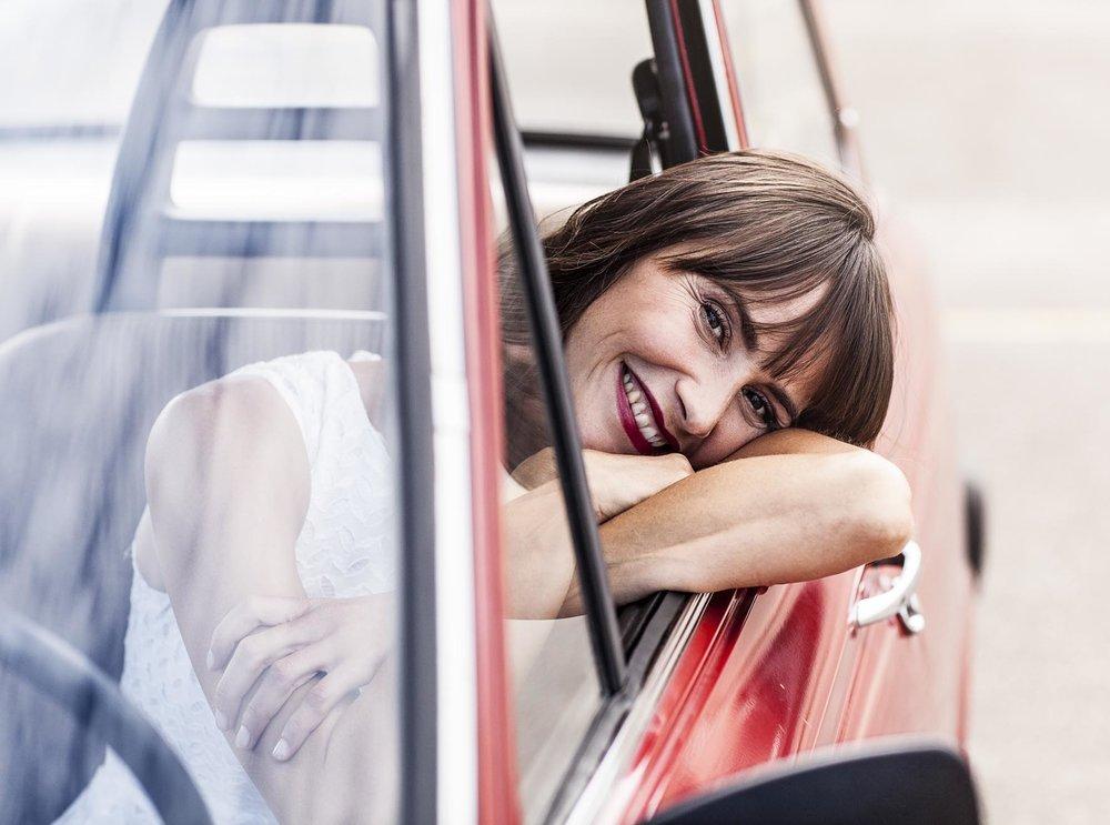 Anne schaut grinsend aus dem Auto