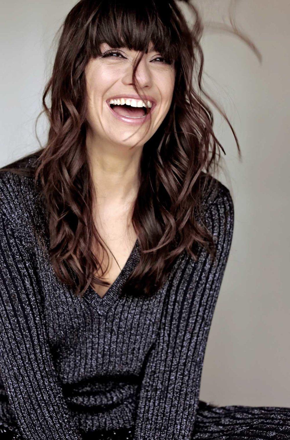 Cora lachend mit braunen Locken