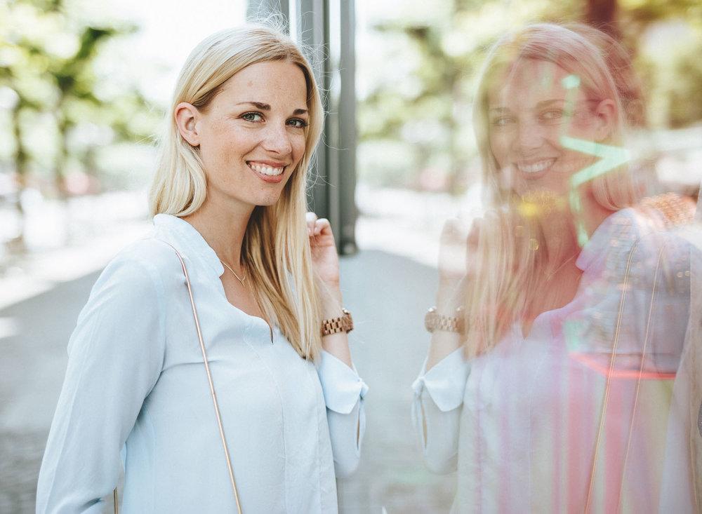 Julia im hellen Look mit Spiegelung im Fenster