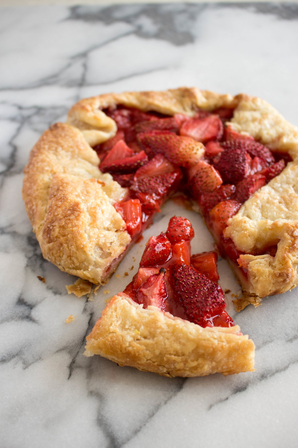strawberry galette  - makes one 8-inch galetteadapted from smitten kitchendough1 1/4 cups all-purpose flour1/2 teaspoon salt1 1/2 teaspoons granulated sugarzest of half a lemon8 tablespoons cold unsalted butter, cut into pieces1/4 cup greek yogurt or sour cream3 tablespoons cold waterstrawberry Filling2 cups strawberries, chopped into pieces3 tablespoons granulated sugar2 tablespoons cornstarchJuice of half a lemonPinch of salttopping1 egg yolk beaten with 1 teaspoon waterturbinado sugar, for sprinkling