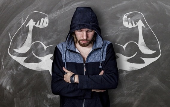 anxious white man with arms akimbo in front of chalkboard with flexing chalk drawn arms
