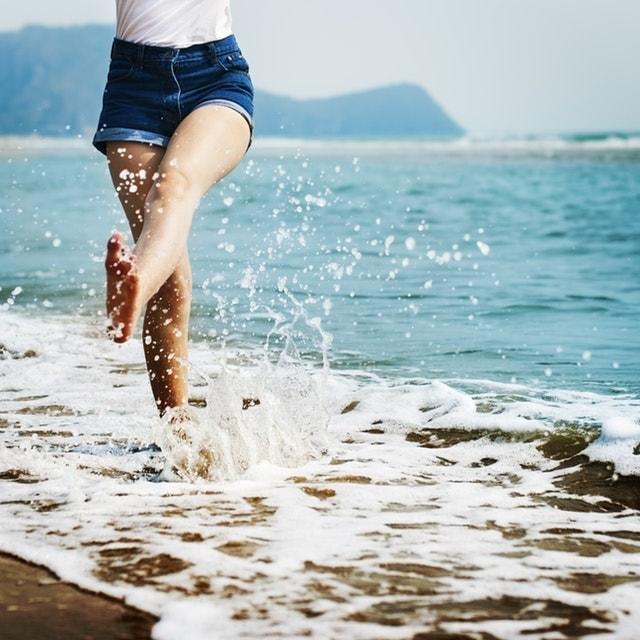 woman kicking up water at the beach