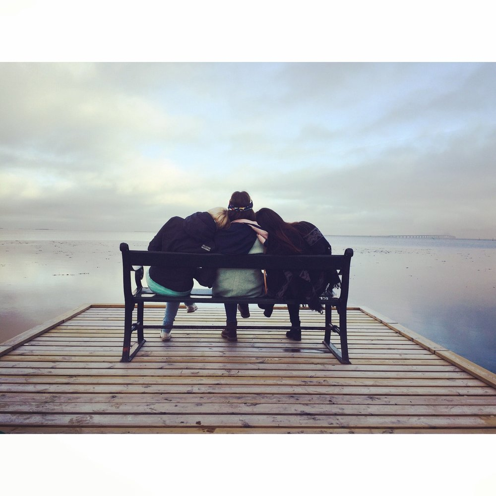 friends on a bench by the water