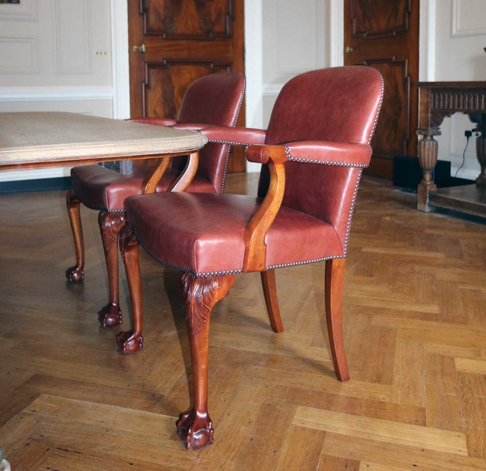 Set of reproduction dining chairs with carved detailing.