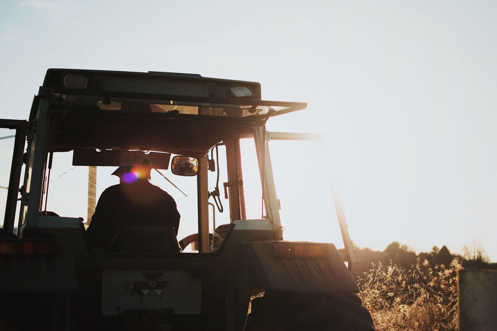 Tractor image on farm with sun flare. Empowering our nation's farmers to create sustainable, prosperous change.