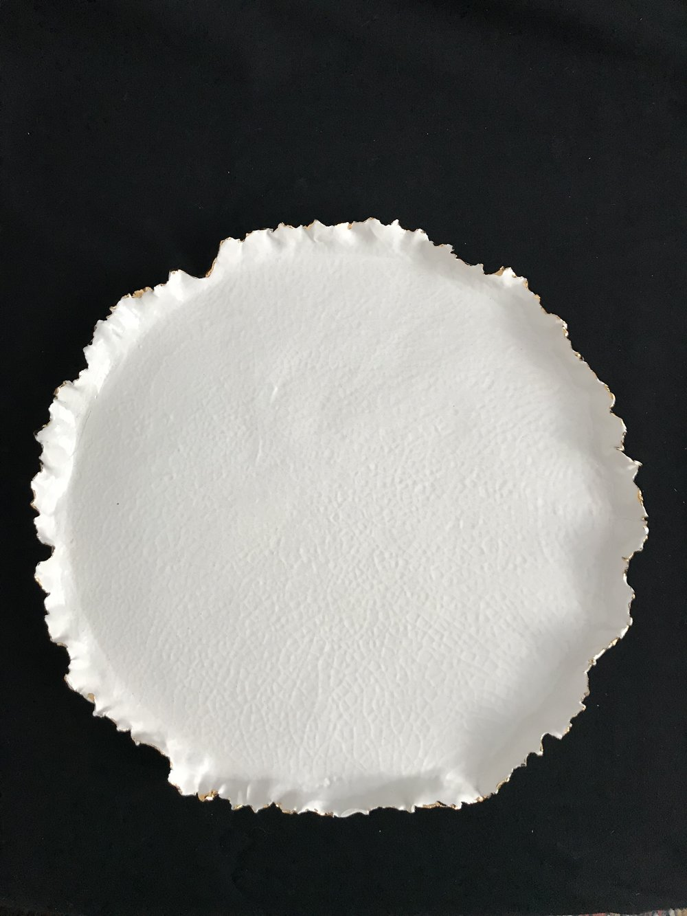 "Victoria Lotus Leaf (Texture),  glazed porcelain with gold interspersed on rim, 1""H rim x 12.75""diameter, 2017. NB: The white of this glaze is warmer than the other pieces. The unique texture was achieved through multiple firings.  $325"