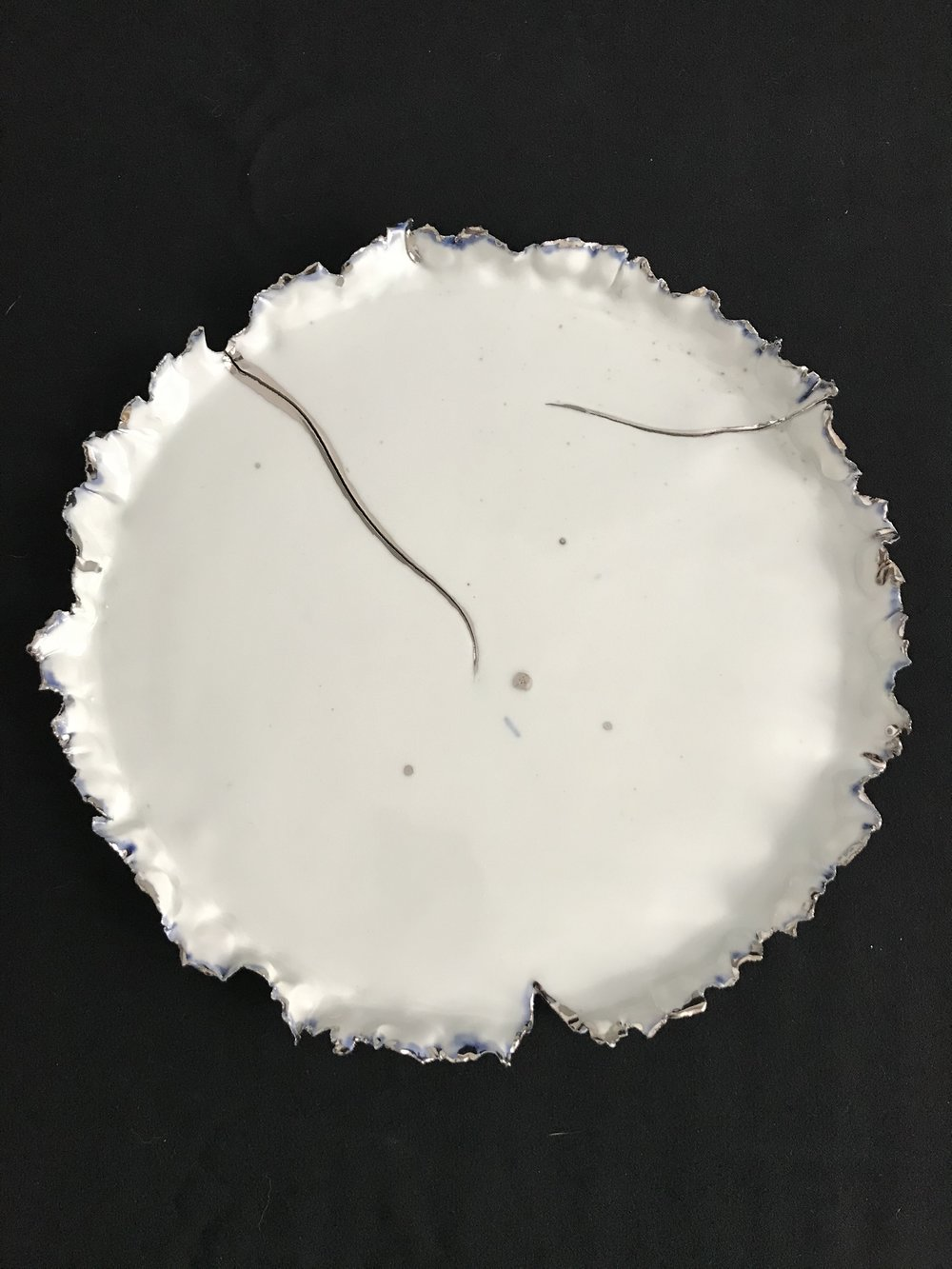 "Victoria Lotus Leaf: How the Light Gets In (Double Crack),  glazed white porcelain with white gold and blue glaze accents interspersed on rim and white gold on crack, 1""H rim x 10.5""diameter, 2018  $325"