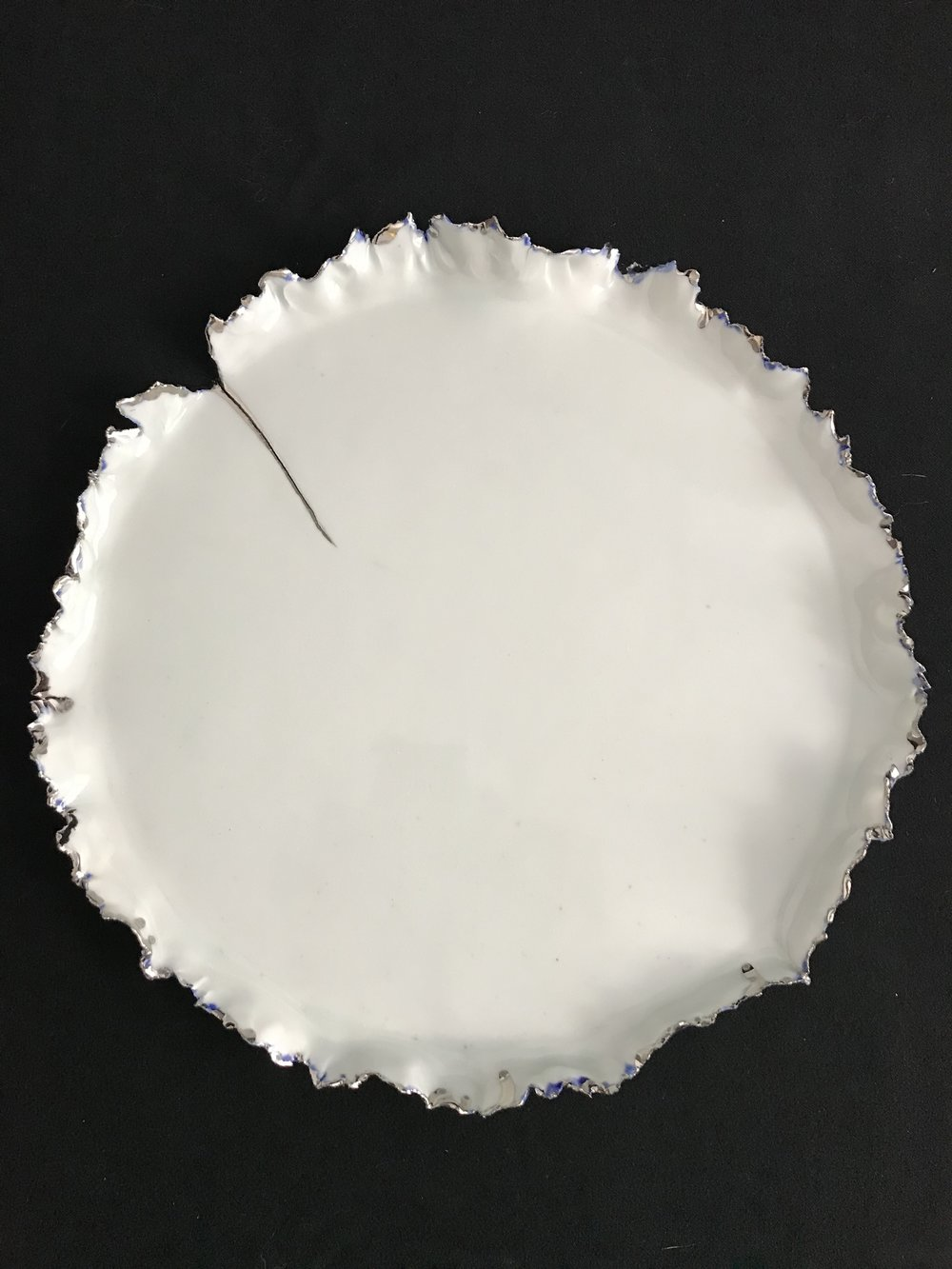"Victoria Lotus Leaf: How the Light Gets In, glazed white porcelain with white gold and blue glaze accents interspersed on rim and white gold on crack, 1""H rim x 10.5""diameter, 2018  SOLD"
