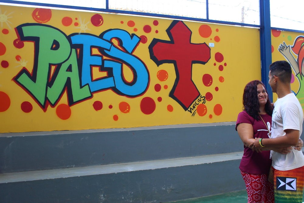 Vinicius, a former student and now a volunteer at House of Hope, and his mother in front of the mural he painted for the new gymnasium at House of Hope.