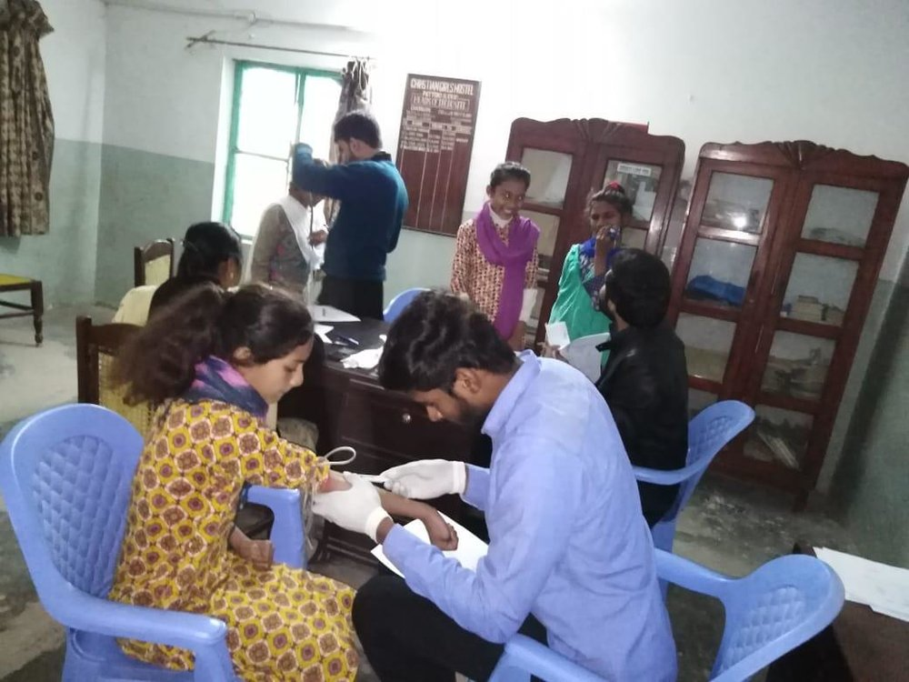 Both girls and boys receive health checkups from visiting doctors.