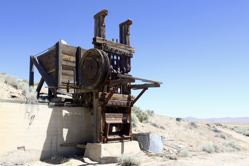 "Old ""5-Stamp"" mill. Ore was loaded above and behind the stamp mill, and as the ore traveled down it was hammered or ""Stamped"" into smaller pieces. There are 5 stamps on this mill. The ore was then taken below to the cyanide ponds for gold separation."