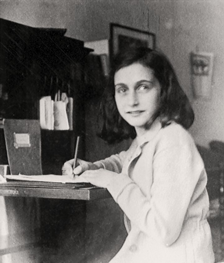 A photo of Anne  writing at her desk  at home at the Merwedeplein, 1941.