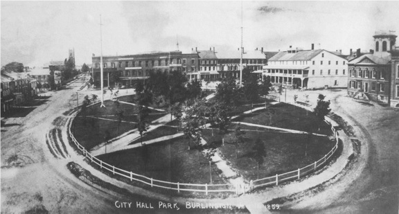 This rare early photograph of Burlington's Courthouse Square, now known as City Hall Park was taken in 1859. The view is looking north from Main Street toward College Street. It shows the oval plan of radiating paths and green that replaced the first courthouse which had been in the center. Along the right hand side of the photograph the following buildings can be seen from right to left: part of the 1854 Town Hall, the 1828 County Courthouse (#3), and Strong's Block, where the county jail and sheriff's office were originally located.